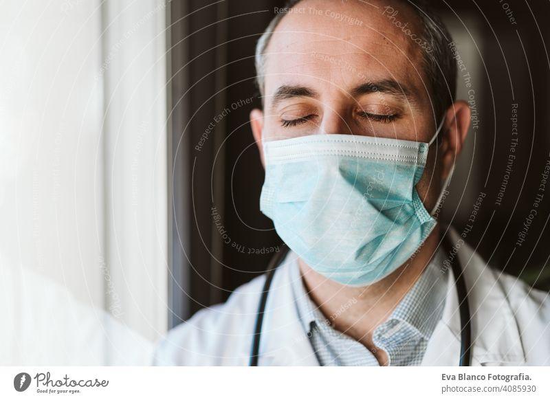 Porträt von Arzt Mann durch das Fenster tragen Schutzmaske und Handschuhe im Haus. Corona Virus Konzept professionell Corona-Virus Krankenhaus arbeiten