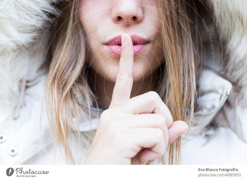 Stille, Geste und Schönheit Konzept - Nahaufnahme Porträt einer jungen Frau hält Finger auf den Lippen Glück schön Mädchen Lifestyle Mode Mantel Natur
