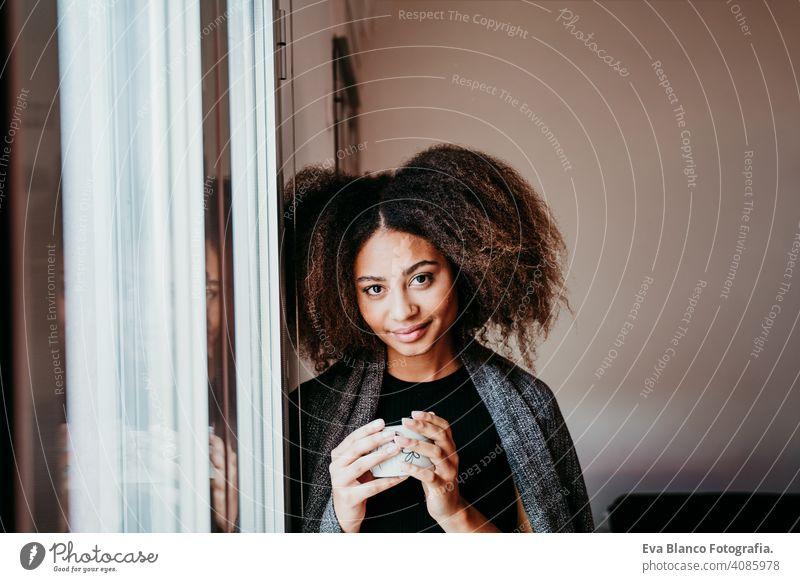 Porträt einer schönen afroamerikanischen jungen Frau am Fenster mit einer Tasse Kaffee in der Hand. Lebensstil im Haus Afroamerikaner heimwärts ethnisch