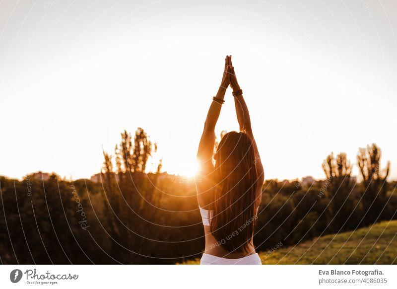 junge schöne asiatische Frau macht Yoga in einem Park bei Sonnenuntergang. Yoga und gesunder Lebensstil Konzept Sommer Glück Genuss Sport Lifestyle sportlich