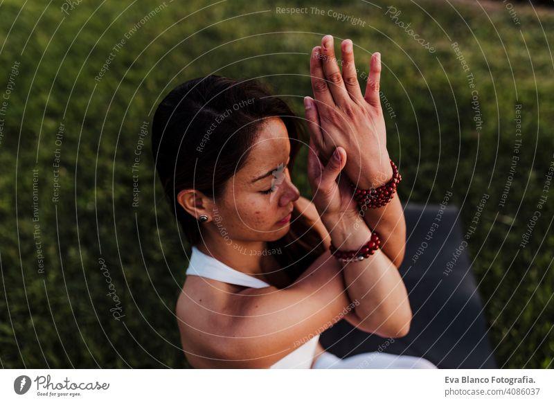 junge schöne asiatische Frau macht Yoga in einem Park bei Sonnenuntergang. Yoga und gesunden Lebensstil Konzept. Sommer Glück Genuss Sport Lifestyle sportlich
