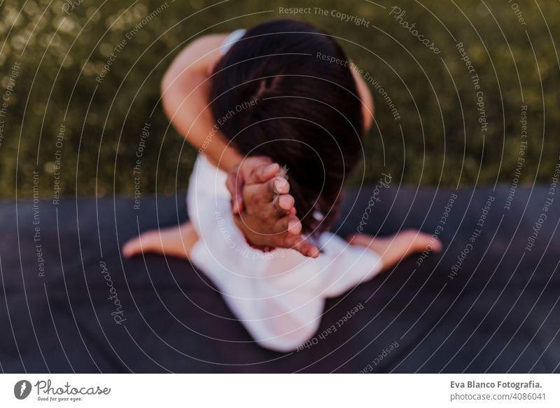junge schöne asiatische Frau macht Yoga in einem Park bei Sonnenuntergang. Yoga und gesunder Lebensstil Konzept. Ansicht von oben. Selektiver Fokus Sommer Glück
