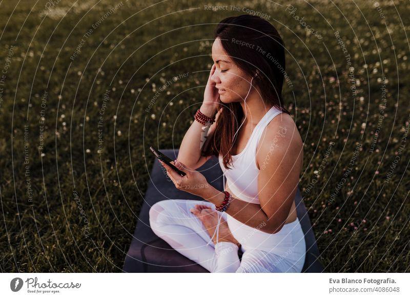 junge schöne asiatische Frau entspannt nach ihrer Yoga-Praxis Musik hören auf Kopfhörer und Handy. Yoga und gesundes Leben Konzept Sommer Glück Genuss Sport