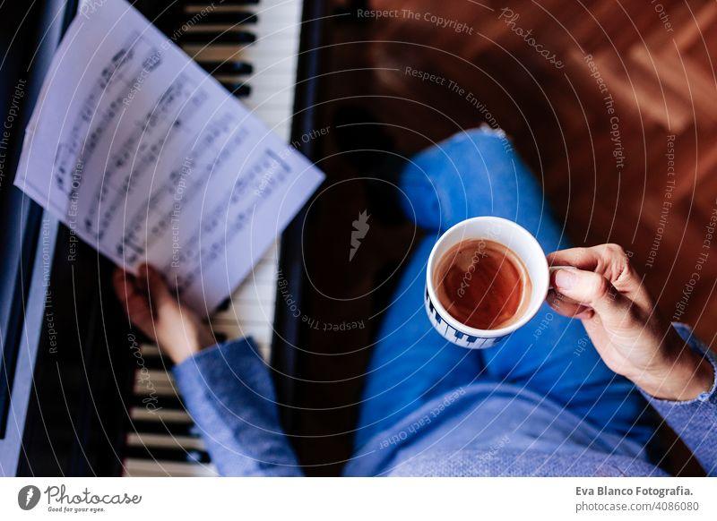 junge unerkennbare Frau, die eine Tasse Kaffee hält und Klavier spielt, indem sie ein Notenblatt liest. Musik-Konzept im Innenbereich. Ansicht von oben Stil