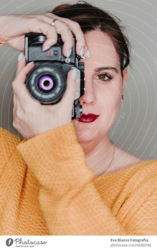 Nahaufnahme Porträt einer jungen Frau, die eine Kamera hält. Fotografie Konzept lässig attraktiv Glück Paparazzi professionell Linse modern Kunst Lifestyle