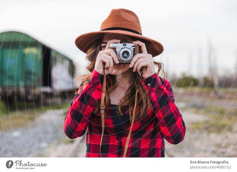 junge schöne Frau trägt lässige Kleidung und einen Hipster-Hut, der ein Bild mit einer Vintage-Kamera macht. Draußen Stadt Hintergrund. Lebensstil. Glück