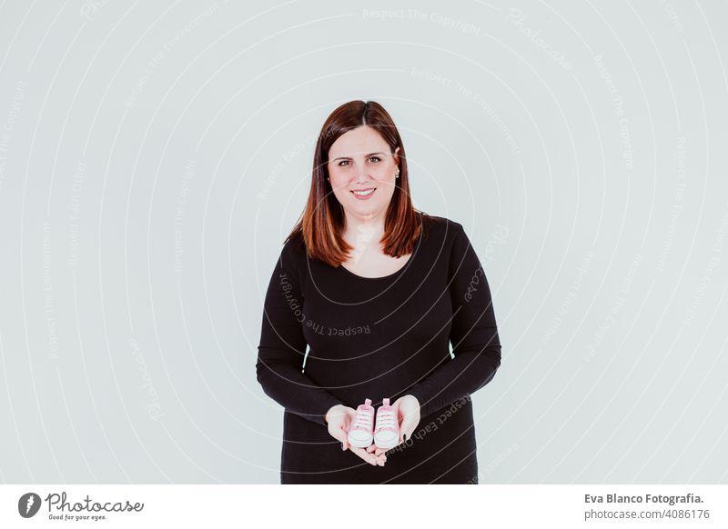 junge schwangere Frau zu Hause hält winzigen rosa Baby-Schuhe. Familie Konzept Mutterschaft Elternschaft erwartend Schwangerschaft heimwärts im Innenbereich