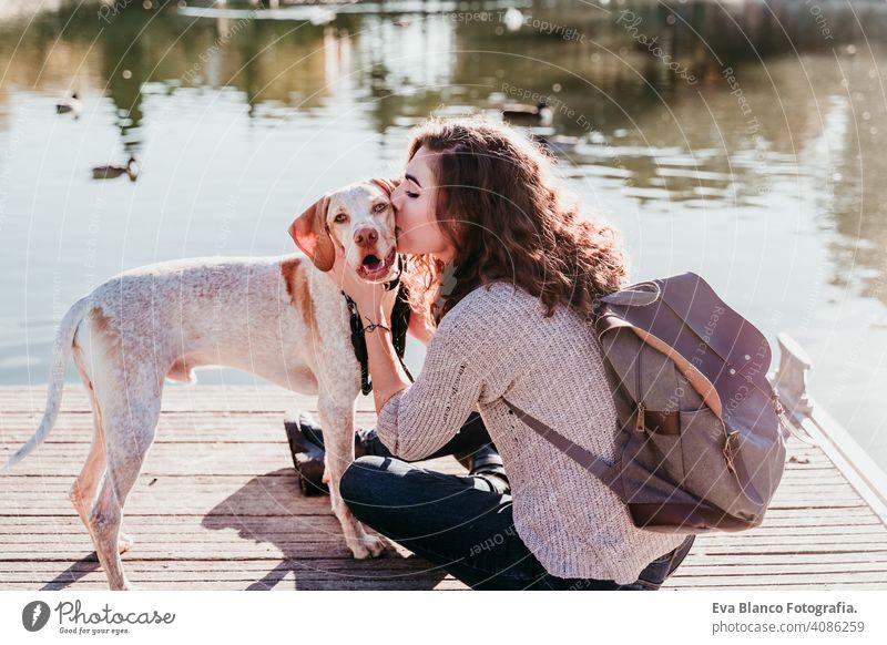 Junge Frau küsst ihren Hund im Freien in einem Park mit einem See. sonniger Tag, Herbstzeit jung Liebe Haustier Besitzer schön Glück Lächeln gemischte Rasse