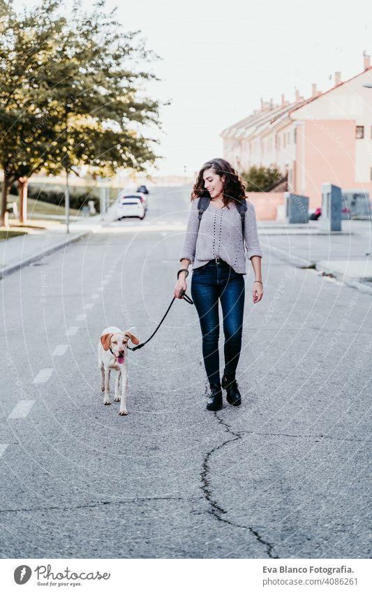 Junge Frau und ihr Hund im Freien, die an der Straße spazieren gehen. Herbstzeit Park jung Liebe Haustier Besitzer sonnig schön Glück Lächeln gemischte Rasse