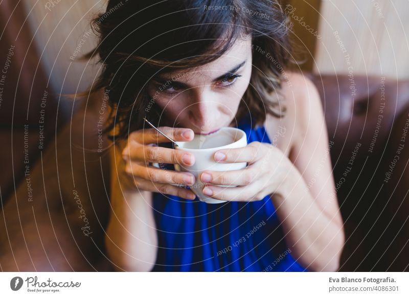 junge schöne Frau genießt eine Tasse Kaffee in einem Café. Laptop neben. Lässiges blaues Kleid. Modernes Leben im Innenbereich Morgen Beteiligung Schönheit