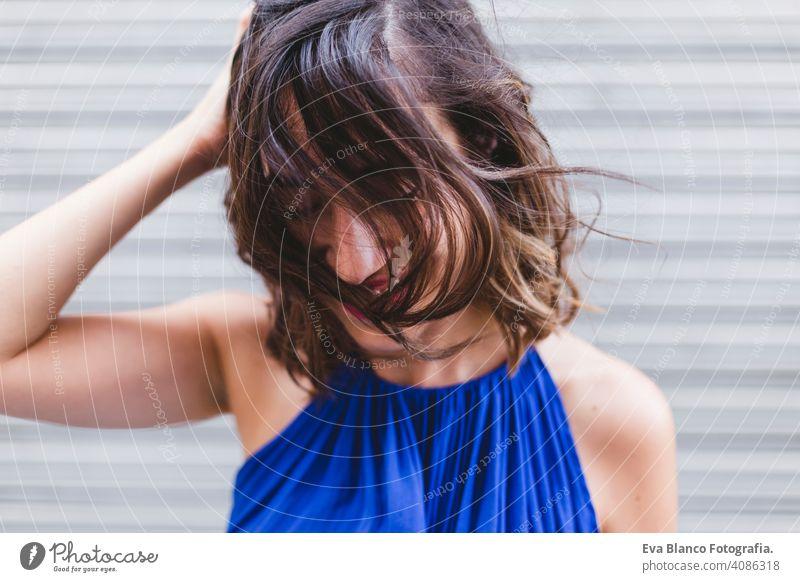 junge schöne Frau lächelnd und mit Haar spielen. Sie ist auf der Straße und trägt ein lässiges blaues Kleid. LIfestyle im Freien, modernes Leben. positiv