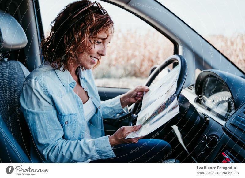 junge schöne Frau lesen eine Karte in einem Auto. Reise-Konzept Landkarte fahren PKW sonnig Sonnenbrille reisen reisend Rad Laufwerk mieten Teilen neu Verkehr