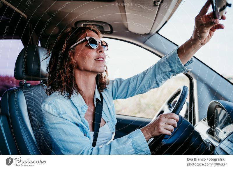junge schöne Frau, die ein Auto fährt und den Rückspiegel einstellt. Reisekonzept fahren PKW sonnig Sonnenbrille reisen reisend Rad Laufwerk mieten Teilen neu