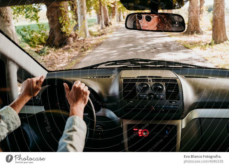 Junge schöne Frau fährt ein Auto. Reise-Konzept. Blick von innen. Weg der Bäume Straße jung fahren PKW sonnig Sonnenbrille reisen reisend Rad Laufwerk mieten