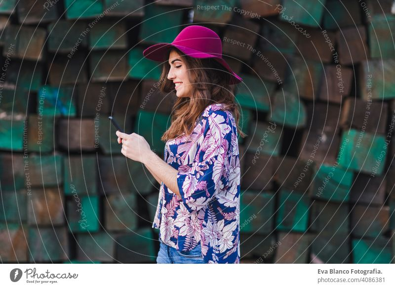 Porträt einer jungen schönen Frau, die legere Kleidung und einen modernen Hut trägt und ihr Mobiltelefon benutzt. Sie steht über grünen Holzblöcken Hintergrund und lächelnd. Lebensstil im Freien.