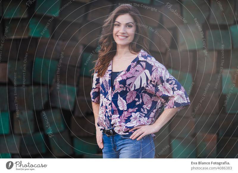 Porträt einer jungen schönen Frau in Freizeitkleidung, stehend über grünen Holzblöcken Hintergrund und lächelnd. Lebensstil im Freien. Nizza Jugend Schüler