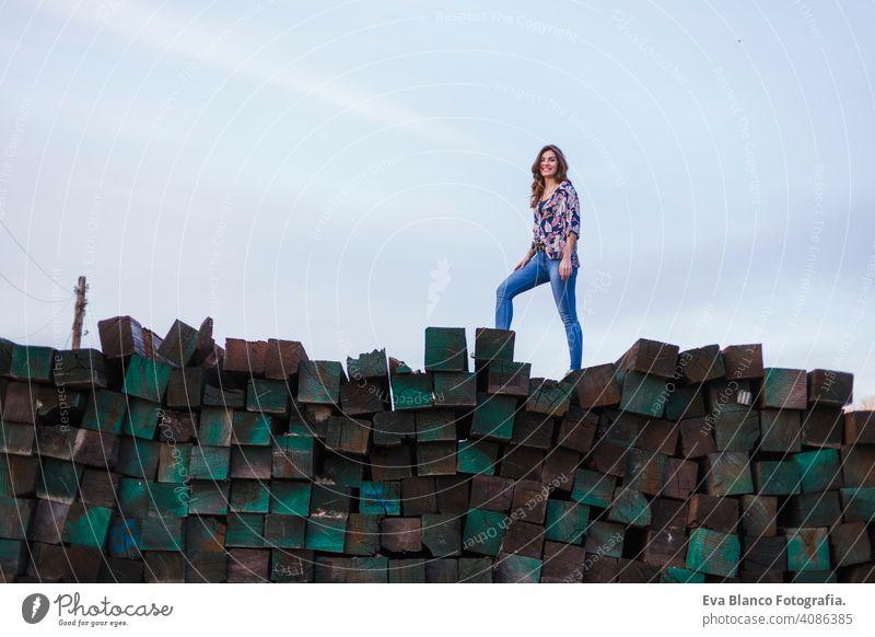 Porträt einer jungen schönen Frau in Freizeitkleidung, die auf einem Berg von grünen Holzblöcken Hintergrund steht und lächelt. Lebensstil im Freien. Jugend