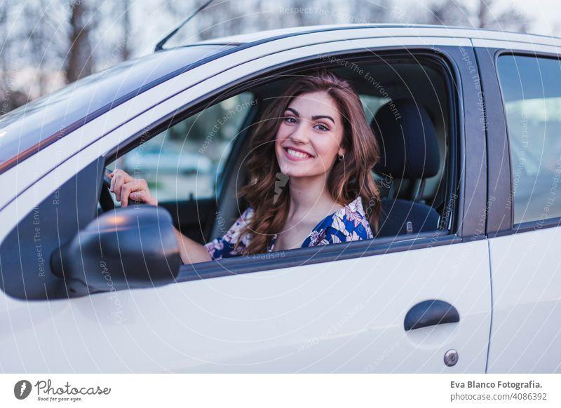 Junge Frau fährt ein Auto in der Stadt. Porträt einer schönen Frau in einem Auto, die aus dem Fenster schaut und lächelt. Reisen und Urlaub Konzepte