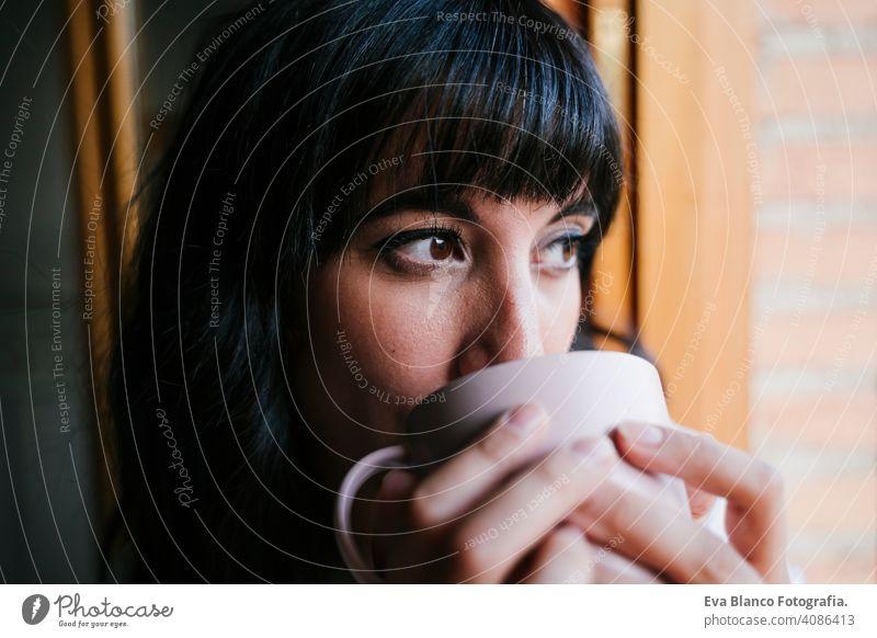 junge kaukasische Frau zu Hause am Fenster mit einer Tasse Kaffee oder Tee. Morgen und entspannen Konzept. Lebensstil im Innenbereich Mädchen bequem