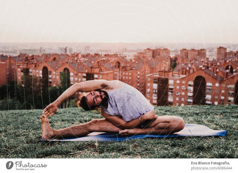 junger Mann in einem Park übt Yoga Sport. Stadt Hintergrund. gesunden Lebensstil. Großstadt Sonnenuntergang Lifestyle Gesundheit Unterlage Sportkleidung