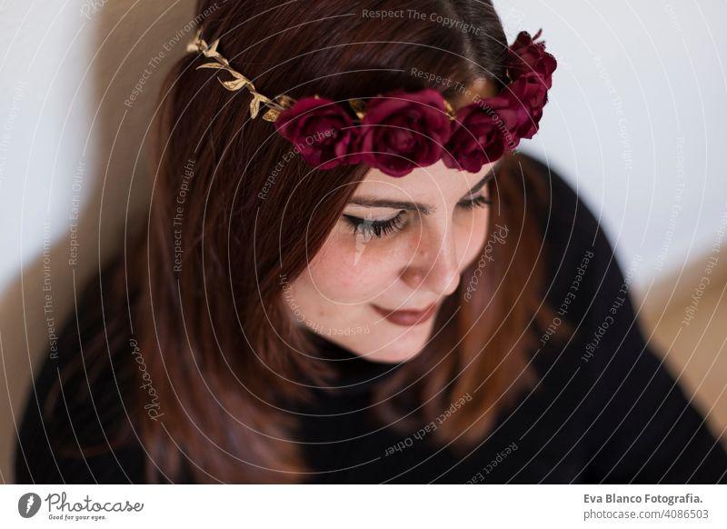 Ansicht von oben Porträt einer jungen schönen Frau trägt einen roten Rosen Kranz. Sie lächelt, in einem Innenraum. Lebensstil Kopf Eleganz erstaunlich Aroma