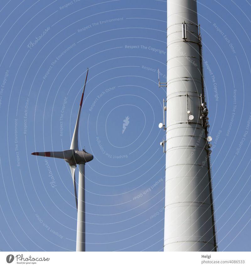 Windkraftanlagen - eine kleinere und eine riesengroße, an deren Mast mehrere Satellitenschüsseln angebracht sind Windrad Strom Stromversorgung Energie