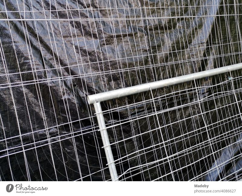 Bauzaun mit grauem Drahtgeflecht und schwarzer Sichtschutz aus Kunststoff auf einer Baustelle am Campus der Goethe Universität in Frankfurt am Main Bockenheim in Hessen