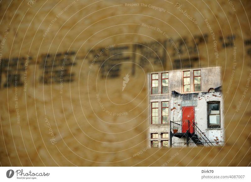 Blick durch den Bauzaun auf ein baufälliges Haus mit roter Tür in Brooklyn, New York Zaun Durchblick Öffnung Loch Guckloch Fassade Fabrik Fabrikhalle