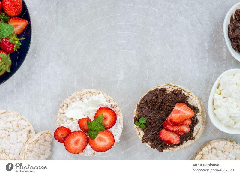 Gesunder Snack aus Reiskuchen mit Haselnussaufstrich, Ricotta-Käse Kuchen Sahne Ansicht Lebensmittel Top Gesundheit Schokolade Frühstück frisch rot Frucht weiß