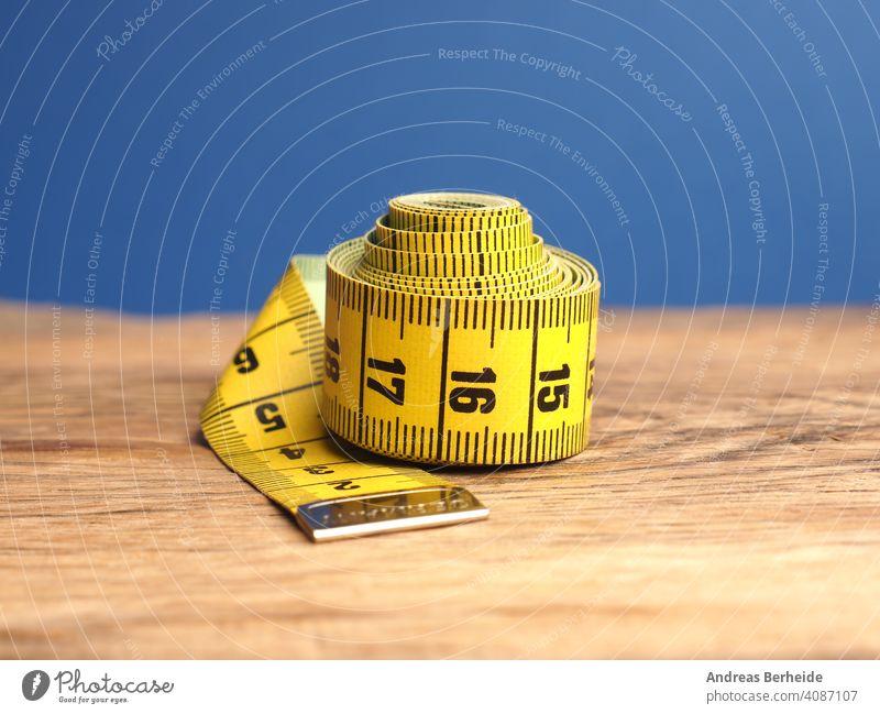 Gelbes Schneidermaßband auf einem Holztisch, Nahaufnahme Klebeband messen Präzision Gesundheit Übergewicht perfekt Zentimeter professionell Ideal