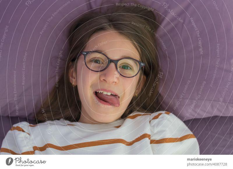 Nahaufnahme eines kleinen kaukasischen Mädchens mit Brille, das auf dem Bett liegt und die Zunge herausstreckt Sehvermögen horizontal Unschuld unschuldig lachen