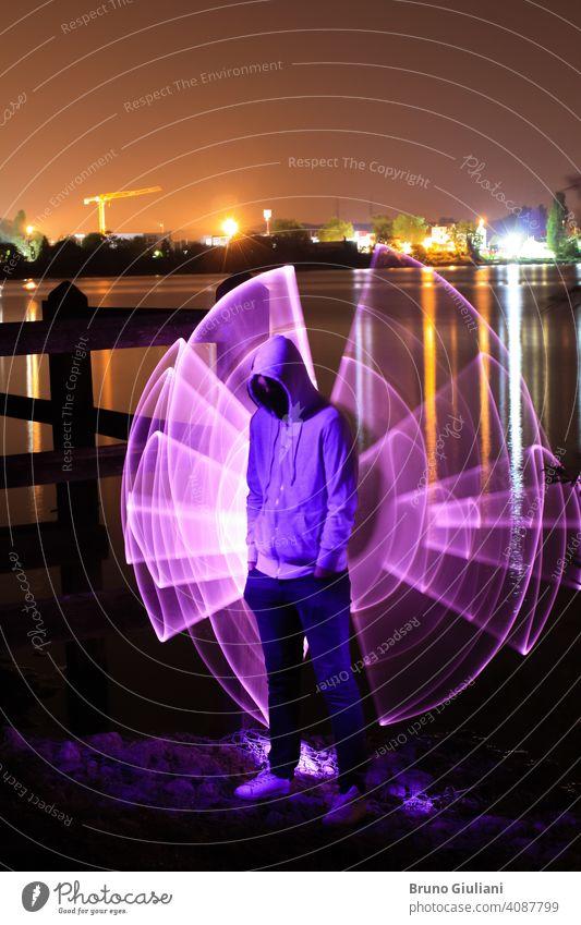 Ein Mann, der mit den Händen in den Taschen und einer Kapuze über dem Kopf steht, steht nachts vor einem See. Violette abstrakte Form mit Lichtschwert dahinter. Lichter der Stadt im Hintergrund.