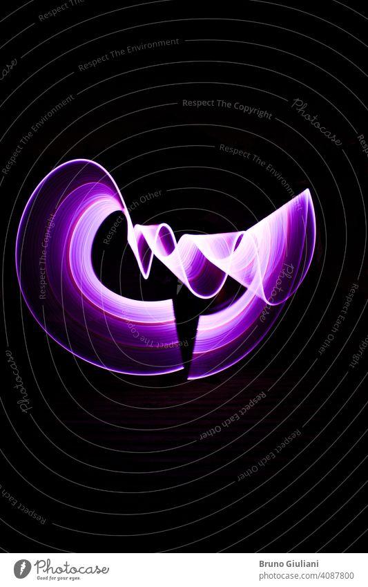 Gekrümmte abstrakte Form mit einem Lichtschwert violett gemacht. Lightpainting Sitzung in der Nacht. Leds Lichteffekt. Lichtmalerei Kunst hell Farbe farbenfroh