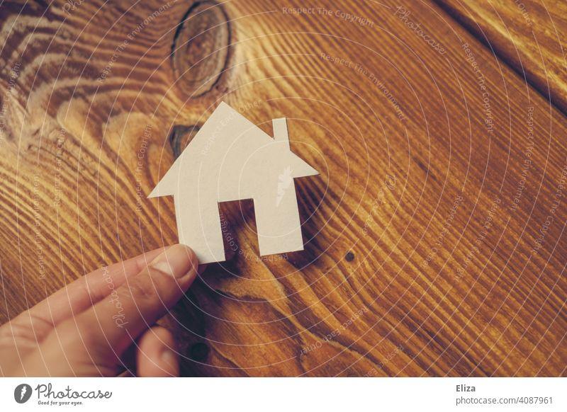 Eine Hand hält ein Haus aus Papier. Eigenheim und Hausbau. Zuhause Traumhaus Holz Haus bauen häuslich Immobilie immobilien Gebäude wohnen zuhause Person Mensch