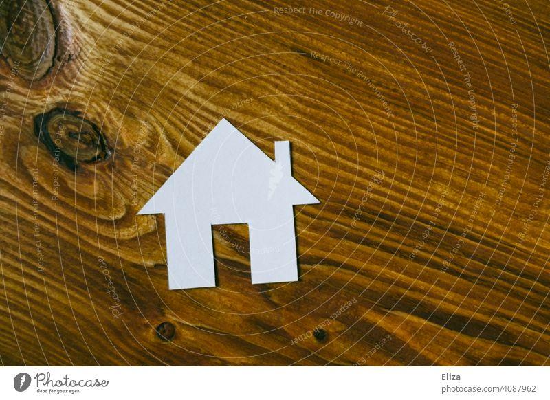 Weißes Haus aus Papier auf Holz. Eigenheim und Hausbau. Zuhause Traumhaus Haus bauen häuslich Immobilie immobilien Gebäude wohnen zuhause