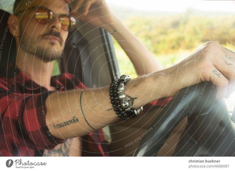 mann im auto - hand am lenkrad portrait auto innen sonnebrille autofahrer armschmuck armreif cool model fahren auto fahren 30 jahre nackter oberkoerper relaxed