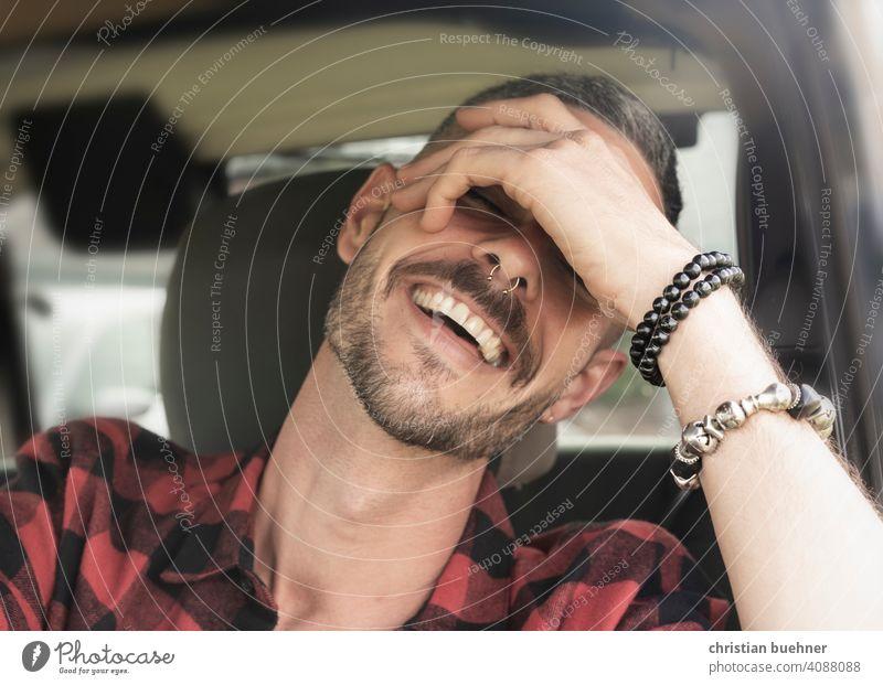 junger mann sitzt lachend im auto portrait 30 jahre hand armreif zaehne fahrersitz happy positiv sonne mode urlaub holilday relaxed entspannt symphatisch