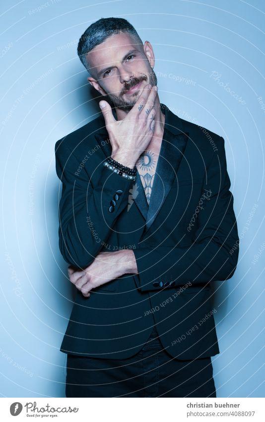 junger tätowierter mann im Anzug portrait model anzug elegant alternativ modern laehelnd symphatisch tatoo hand bart blau studio parfume edel gutaussehend