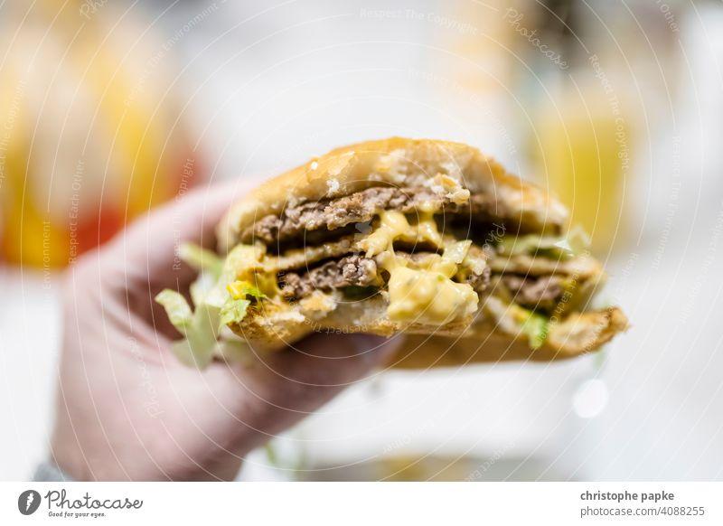 Hamburger in Hand Fastfood Ernährung Ich-Perspektive Egoperspektive pov Lebensmittel Fleisch Mittagessen ungesund Cheeseburger Burger Snack Nahaufnahme Mahlzeit