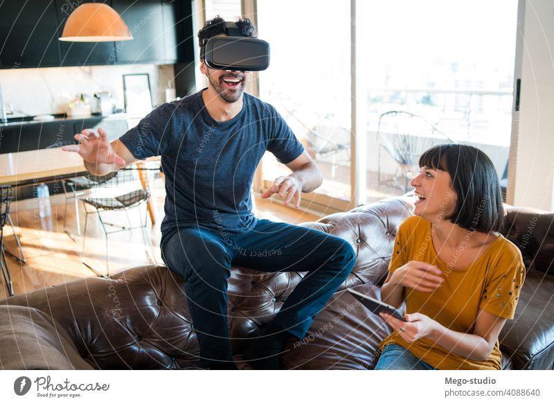 Ein Paar spielt Videospiele mit einer VR-Brille. Realität digital Tablette Spielen Schutzbrille Simulation Gerät Entertainment im Innenbereich jung Headset