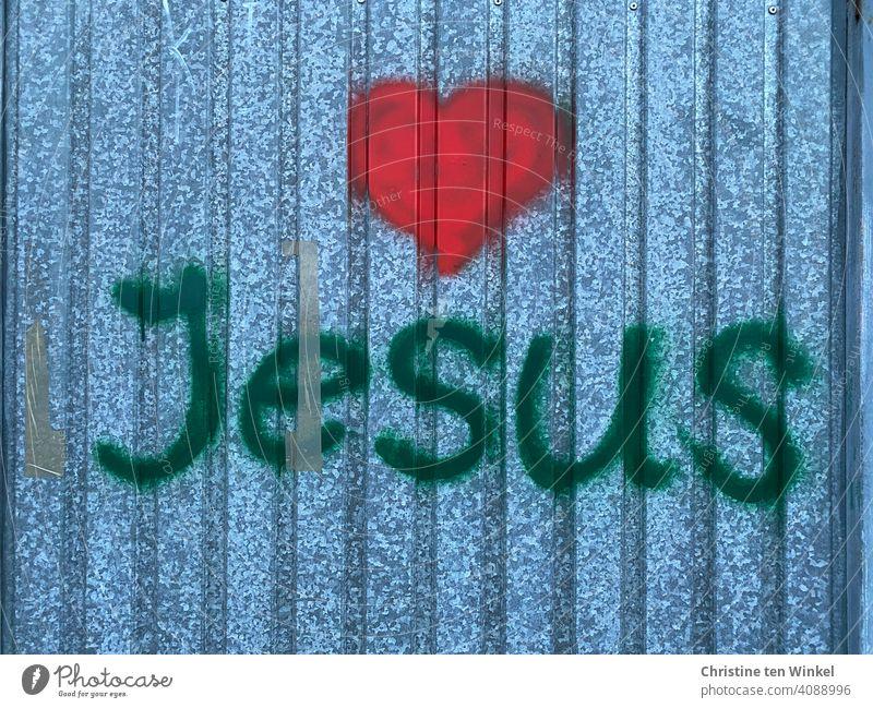 Graffiti mit dem Namen Jesus und einem roten Herz auf einer Metallfassade rotes Herz Liebe Metallwand Ostern Karwoche Glaube Hoffnung Kirche Jesus Christus