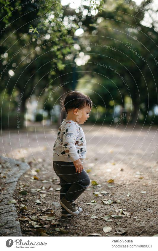 Kind geht im Park spazieren Kindheit Seitenansicht authentisch Kindheitserinnerung mehrfarbig Tag 1-3 Jahre Freude Kaukasier Außenaufnahme Farbfoto Glück