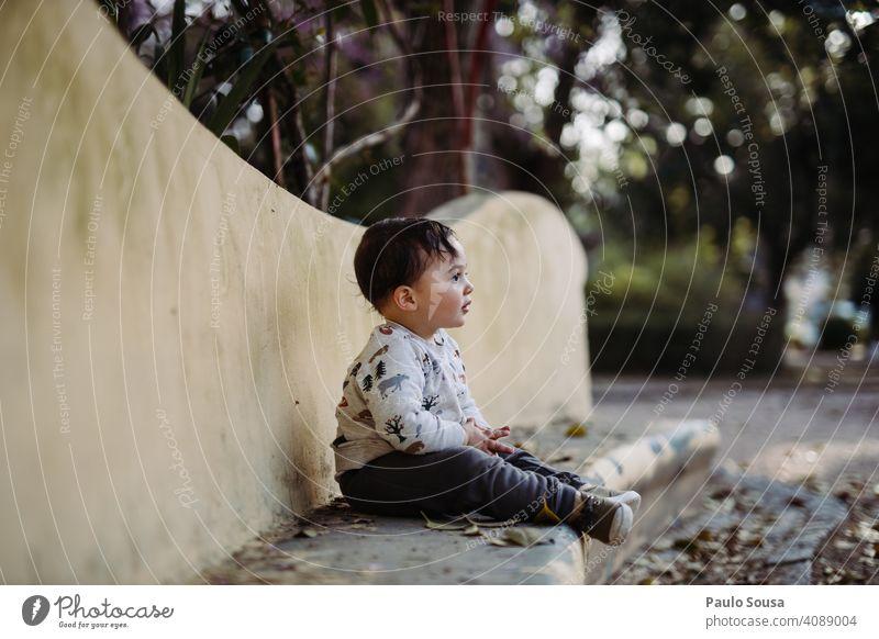 Junge sitzend im Park Kind 1-3 Jahre Kaukasier Sitzen niedlich Farbfoto Kindheit Kleinkind Mensch Lifestyle Außenaufnahme Tag Freude Kinderspiel authentisch