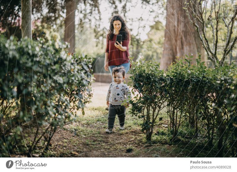 Mutter fotografiert Kind beim Spielen im Park Fotografieren Mutter mit Kind Kaukasier 1-3 Jahre Spaß haben Leben Eltern Liebe Zusammensein Freude Glück