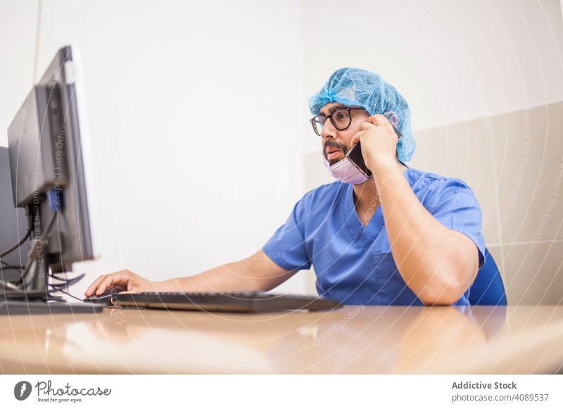 männlich Chirurgie am Computer und Smartphone arbeiten vor der Operation Erwachsener Krankenhaus medizinisch benutzend Kaukasier Arzt Medizin Büro Uniform