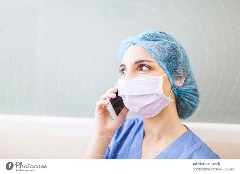 Weibliche Chirurgin benutzt ihr Smartphone in einem Krankenhaus Job Körperhaltung überdrüssig im Innenbereich Hut Wand Operationssaal professionell Flur weiß