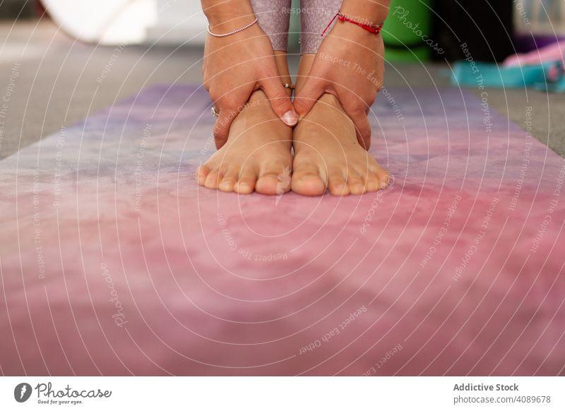 Gesichtslose athletische Frau macht stehende Yoga-Pose sportlich Fuß Hände beweglich positionieren rosa Unterlage Stehen Sport Erholung praktizieren Meditation
