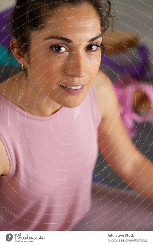 Frau in Sportkleidung ruht und schaut in die Kamera Yoga Pose Gerät sportlich jung attraktiv ernst beweglich Sitzen positionieren brünett Erholung Harmonie