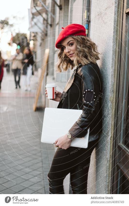 Frau mit Getränk auf der Straße trinken Großstadt Gebäude Imbissbude Tasse stylisch jung Baskenmütze Outfit Takeout Dame Lehnen Wand zum Mitnehmen Kaffee Tee