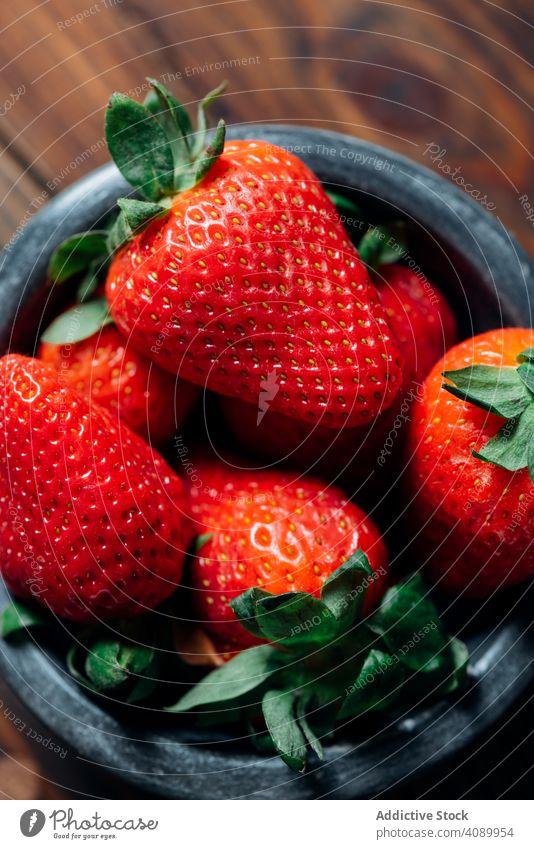 Frische reife Erdbeeren in schwarzem Beton Schüssel. Holz Hintergrund saftig saisonbedingt roh Gesundheit Frühstück organisch oben Feinschmecker Frucht Frühling